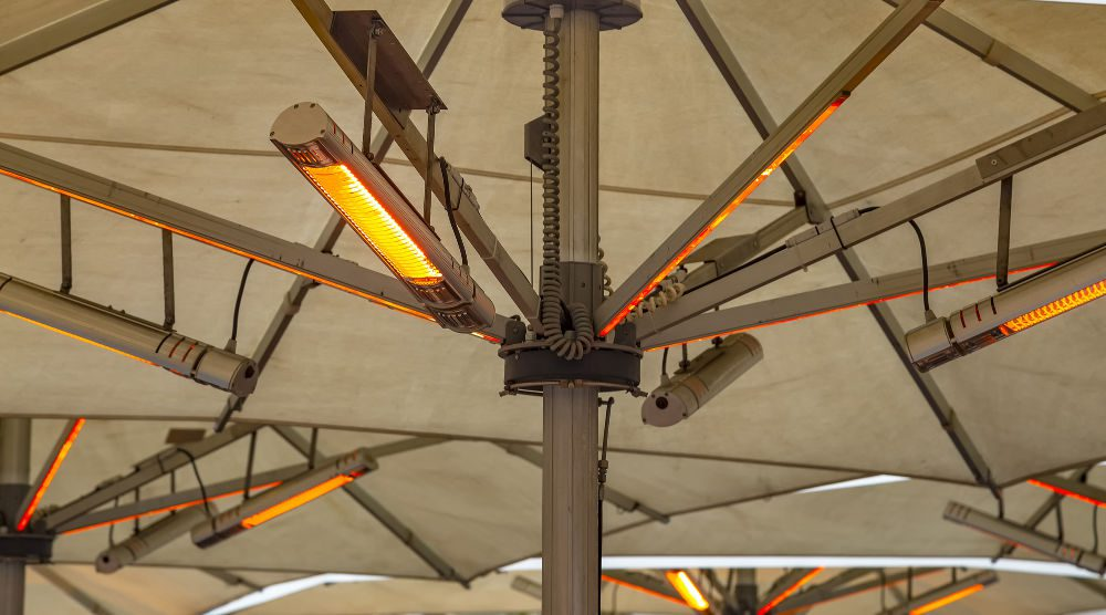 Outdoor electric heating infrared lamps under umbrella in street cafe